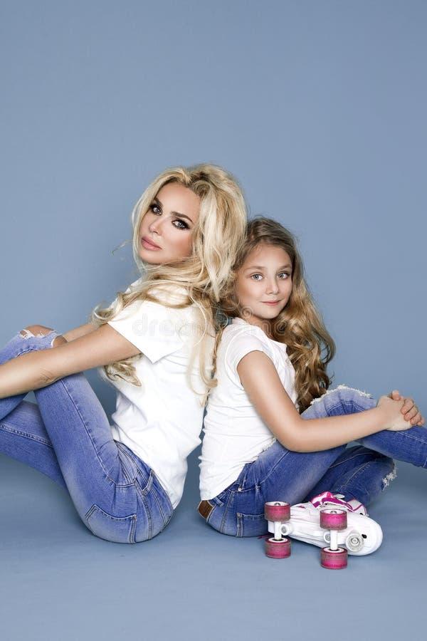 A mãe nova bonita com sua filha vestiu-se na roupa do verão e as calças de brim e os rolos imagem de stock
