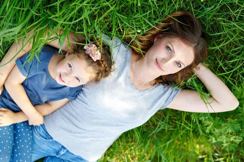 Mãe nova bonita e filha pequena que encontram-se na grama verde e no descanso foto de stock royalty free