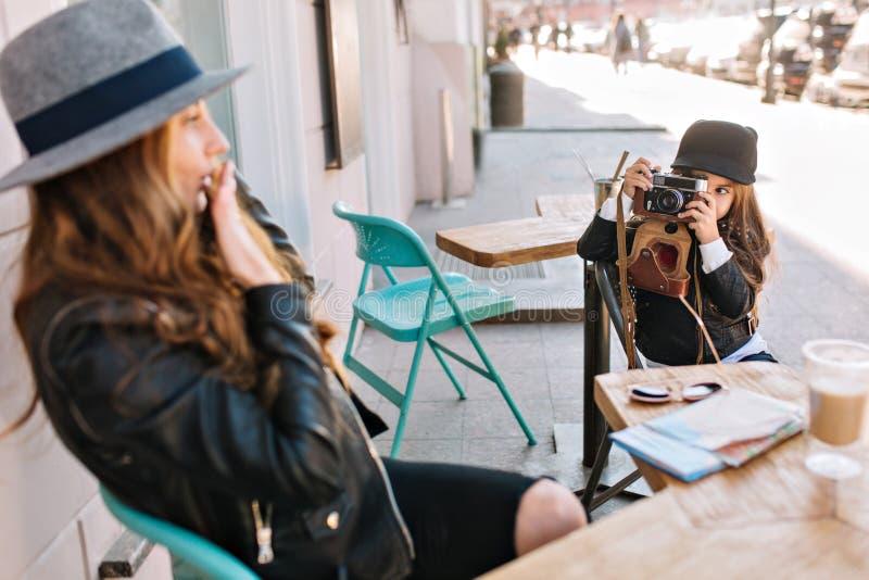 Mãe nova bonita e sua filha bonito que sentam-se fora no café no fundo ensolarado da cidade Eles à moda vestido imagem de stock