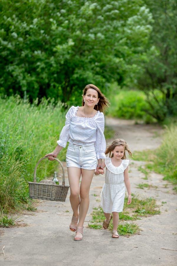 Mãe nova bonita e sua filha pequena no vestido branco que tem o divertimento em um piquenique Andam ao longo da estrada no parque imagens de stock