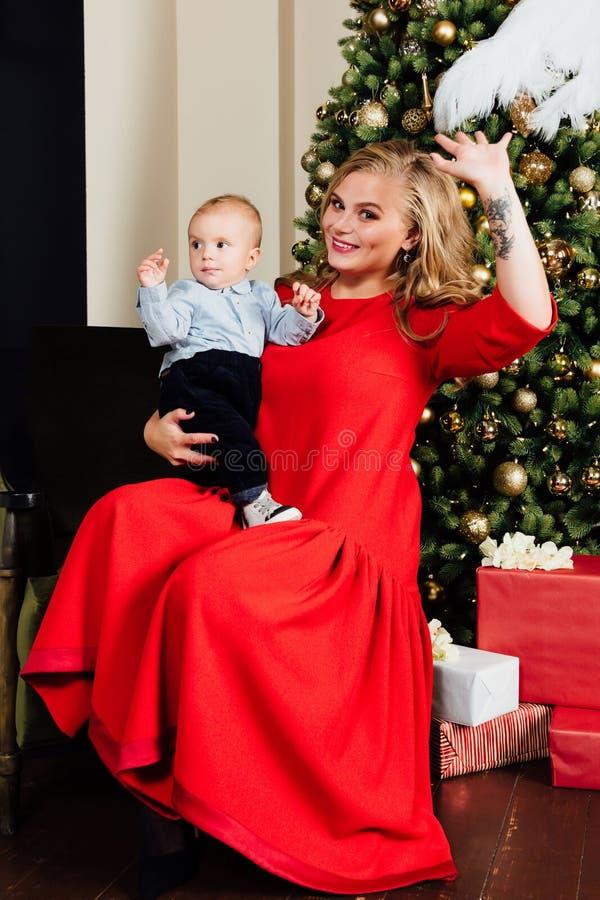 Mãe nova bonita feliz e seu bebê de um ano pequeno que sentam-se na poltrona fotografia de stock royalty free