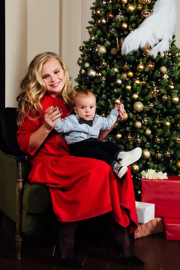 Mãe nova bonita feliz e seu bebê de um ano pequeno que sentam-se na poltrona fotos de stock