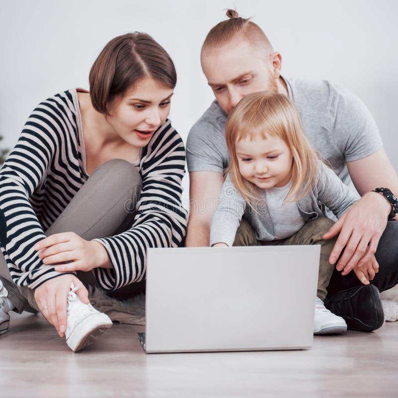 A mãe nova bonita, o pai e sua filha estão usando o portátil, estão falando e estão sorrindo ao sentar-se no sofá em fotos de stock royalty free