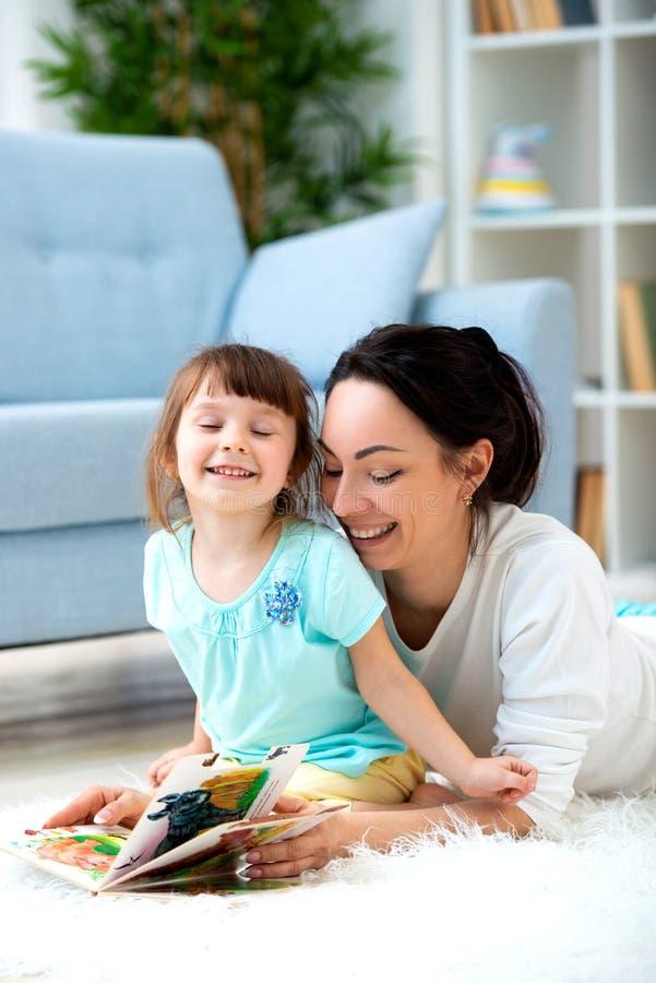 Mãe nova bonita que lê um livro a sua filha que senta-se no tapete no assoalho na sala Leitura com crianças fotos de stock royalty free