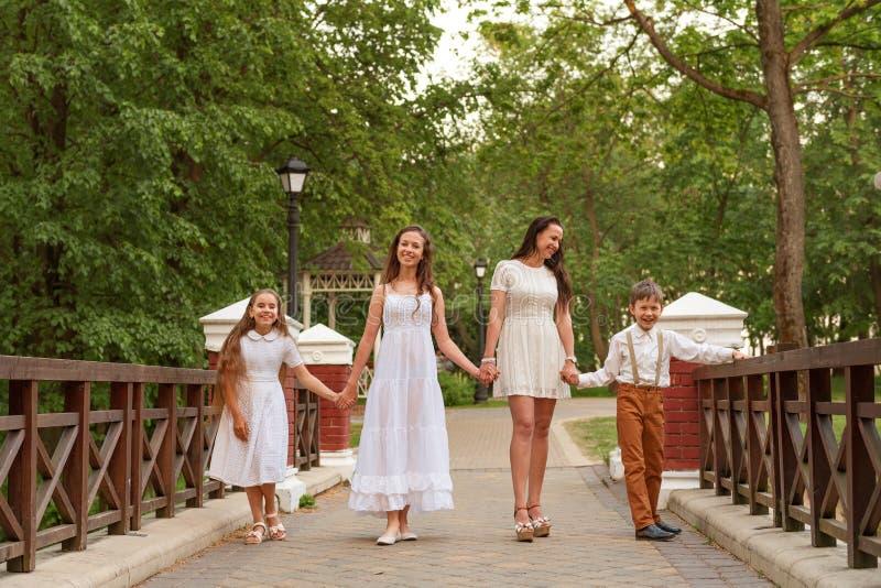 A mãe nova com as crianças no branco veste o passeio ao longo da ponte que guarda as mãos e que ri o sorriso imagens de stock