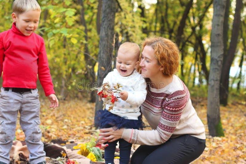 A mãe nova com as duas crianças felizes tem o divertimento fotografia de stock