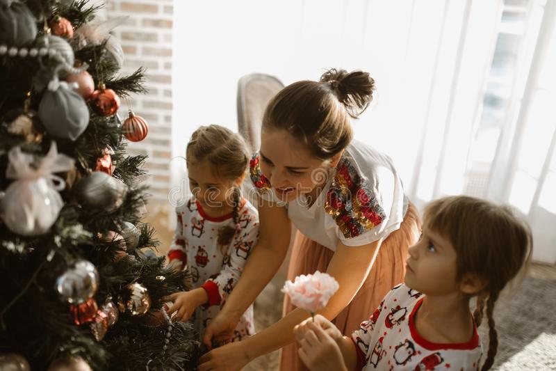 A mãe nova com as duas filhas pequenas nos pijamas decora uma árvore de ano novo na sala acolhedor com com a janela clara grand foto de stock