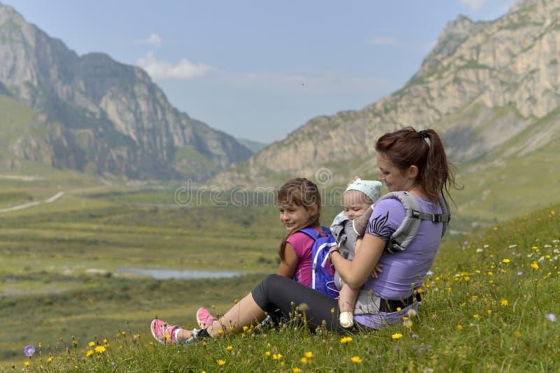 Mãe nova com cursos das crianças nas montanhas imagens de stock royalty free