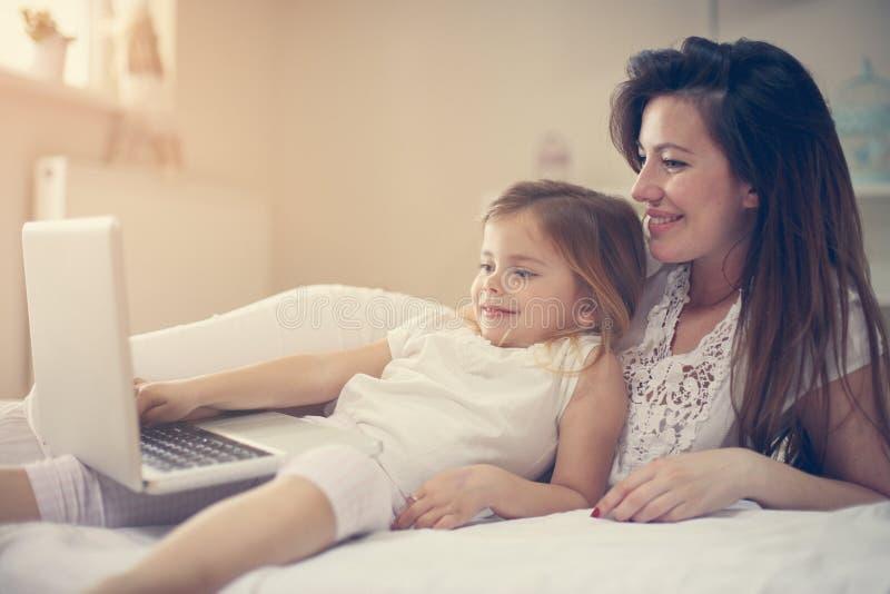 Mãe nova com a filha que usa o portátil na cama em casa fotos de stock royalty free