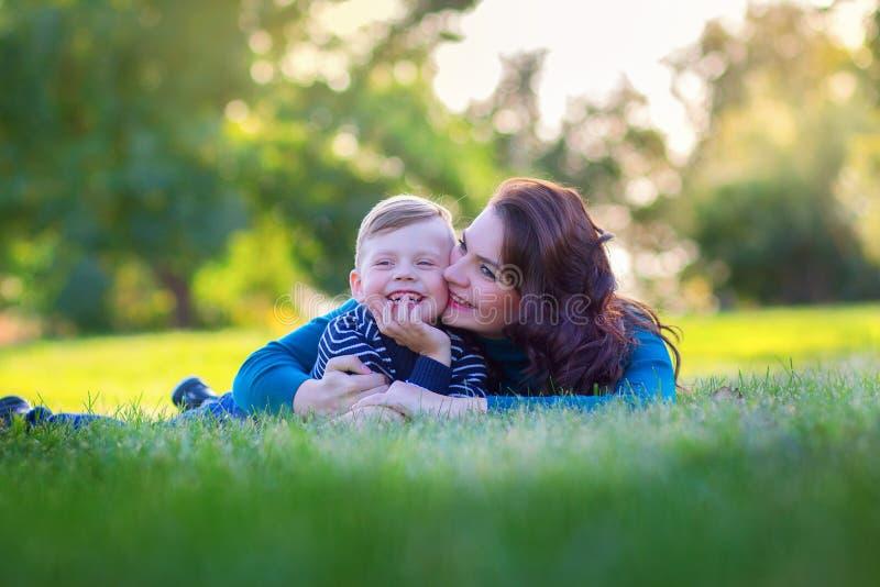 Mãe nova com a mentira do filho em uma grama no parque e no abraço fotos de stock