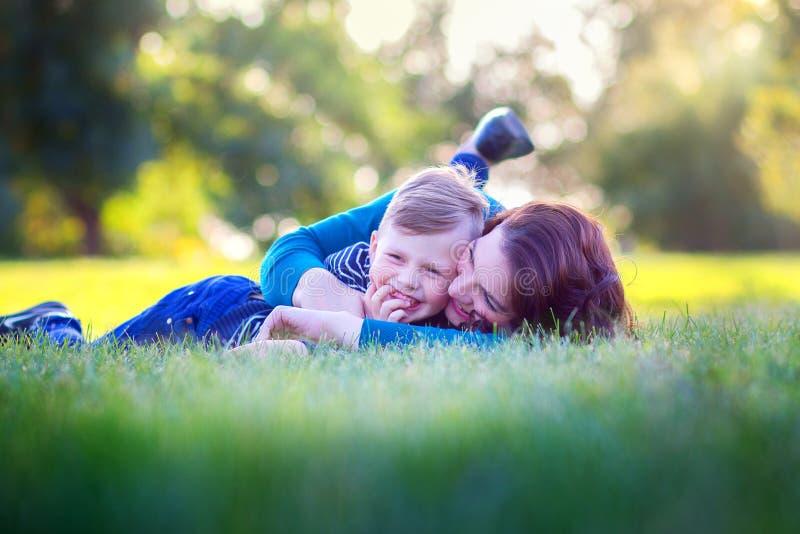 Mãe nova com a mentira do filho em uma grama no parque e alegremente no abraço imagens de stock royalty free