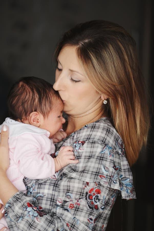 Mãe nova com o bebê recém-nascido bonito imagem de stock