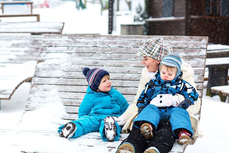 Mãe nova com os dois meninos pequenos da criança que sentam-se no banco no parque do inverno Mulher que joga e que abraça com os  fotografia de stock