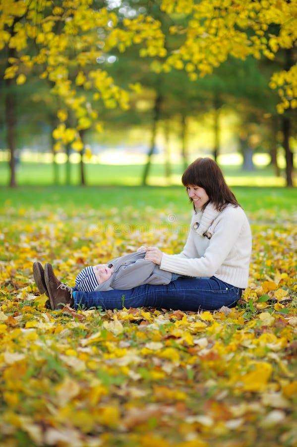 Mãe nova com seu bebê pequeno no parque do outono foto de stock
