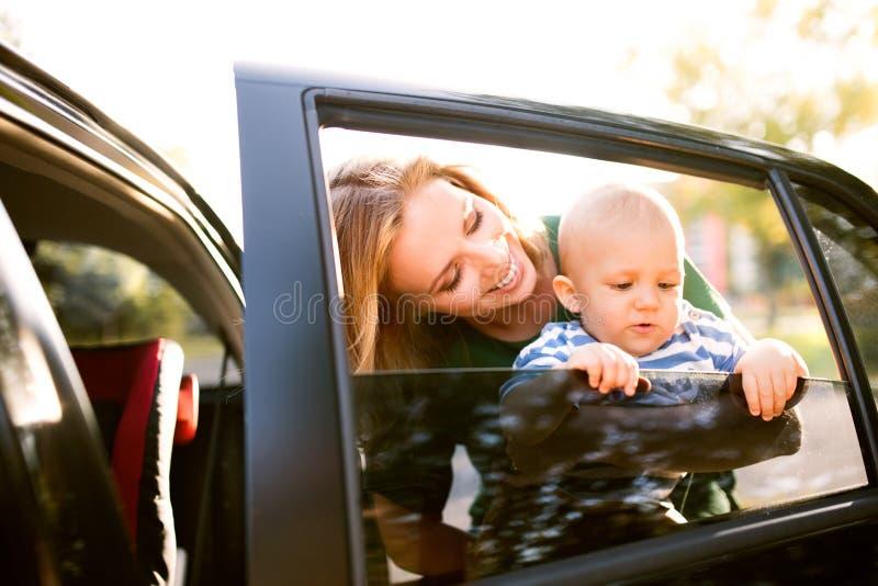 Mãe nova com seu bebê pequeno que está pelo carro foto de stock