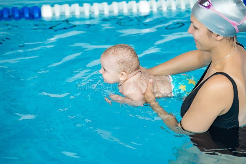 Mãe nova com seu filho pequeno, atendendo a lições da natação para fotografia de stock