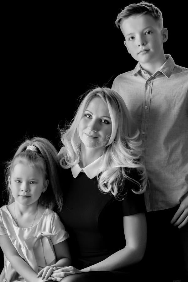 Mãe nova com seu pH preto e branco do estúdio do filho e da filha imagem de stock