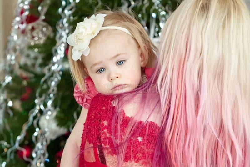 Mãe nova com um bebê cansado na frente da árvore do xmas Retrato da família do Natal imagens de stock royalty free