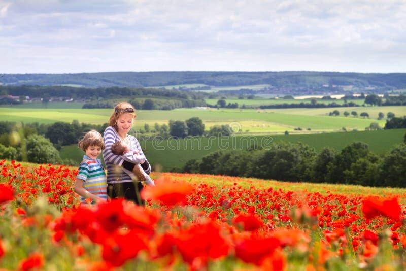 Mãe nova com um filho e uma filha recém-nascida no campo de flor lindo da papoila fotos de stock