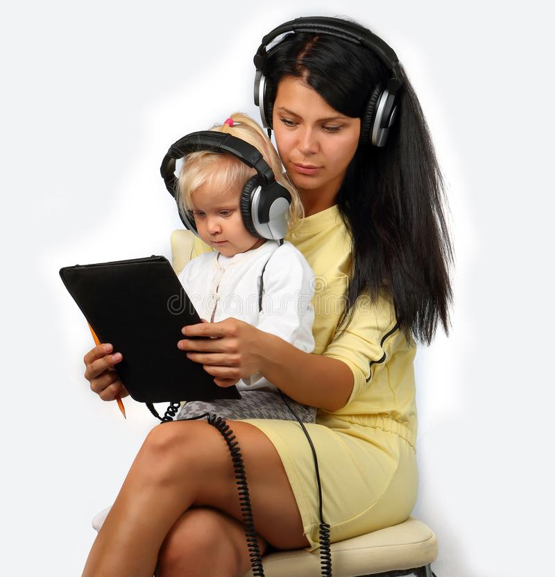 Mãe nova com uma criança nos fones de ouvido e com uma tabuleta fotografia de stock