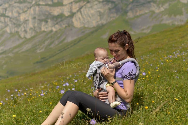 Mãe nova com uma criança pequena no cursos trouxa-levando nas montanhas fotos de stock royalty free