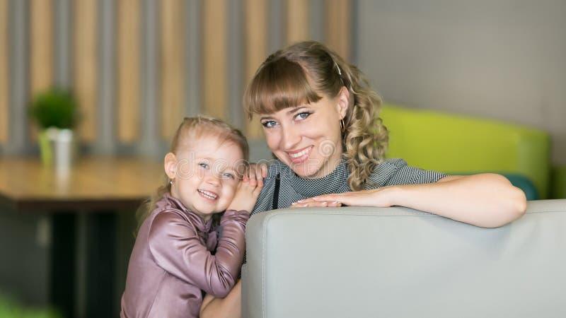 Mãe nova com uma filha pequena em um café imagens de stock royalty free