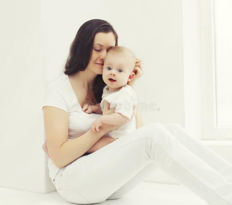 Mãe nova da foto feliz com bebê em casa na sala branca fotografia de stock