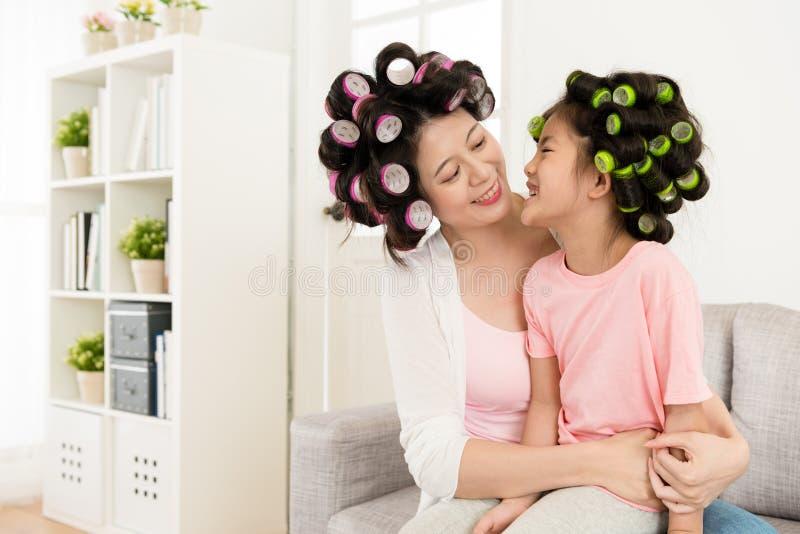 Mãe nova de sorriso que abraça a filha pequena fotografia de stock