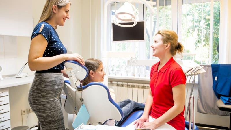 Mãe nova de sorriso que fala ao dentista pediatra no escritório do dentista fotos de stock royalty free
