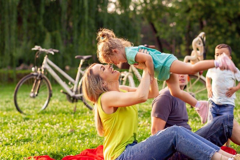 Mãe nova do tempo feliz da família que aumenta sua criança da menina acima imagens de stock royalty free
