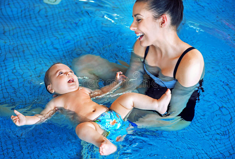 Mãe nova e bebê que relaxam na piscina fotos de stock royalty free