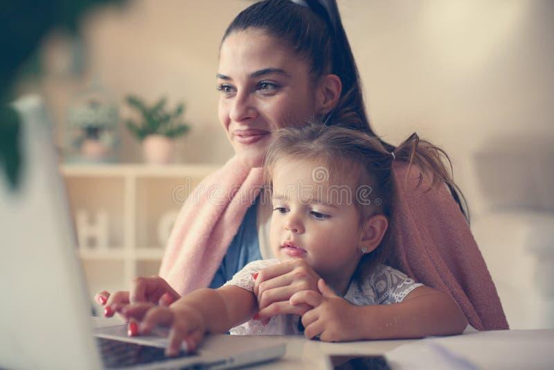Mãe nova e filha em casa que datilografam no portátil imagem de stock