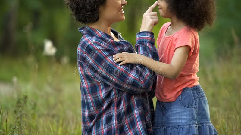 Mãe nova e filha pequena bonito que nuzzling e que riem junto, felicidade fotos de stock