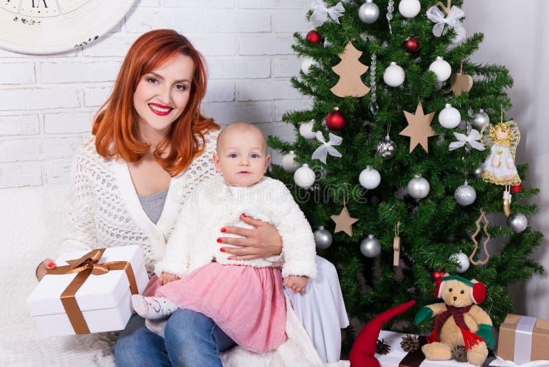 Mãe nova e filha pequena com a caixa de presente na frente de Chris imagens de stock royalty free