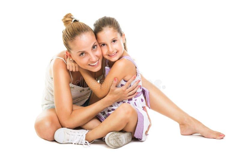 Mãe nova e filha que abraçam e que sorriem foto de stock royalty free
