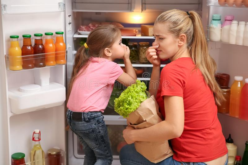 Mãe nova e filha que guardam a causa dos narizes do cheiro mau do refrigerador em casa fotografia de stock