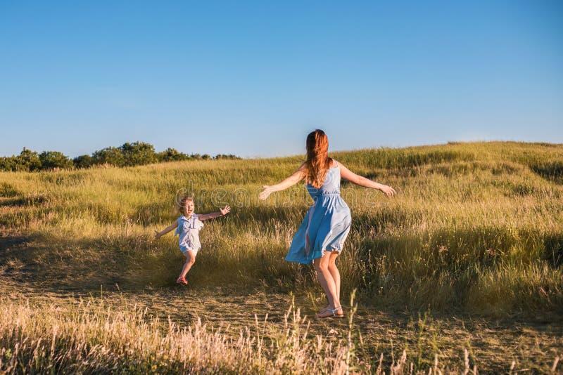Mãe nova e filha que jogam no campo dourado da luz do sol fotografia de stock