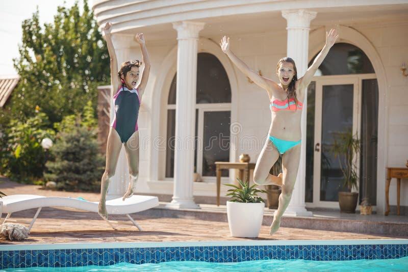 Mãe nova e filha que saltam na piscina imagem de stock