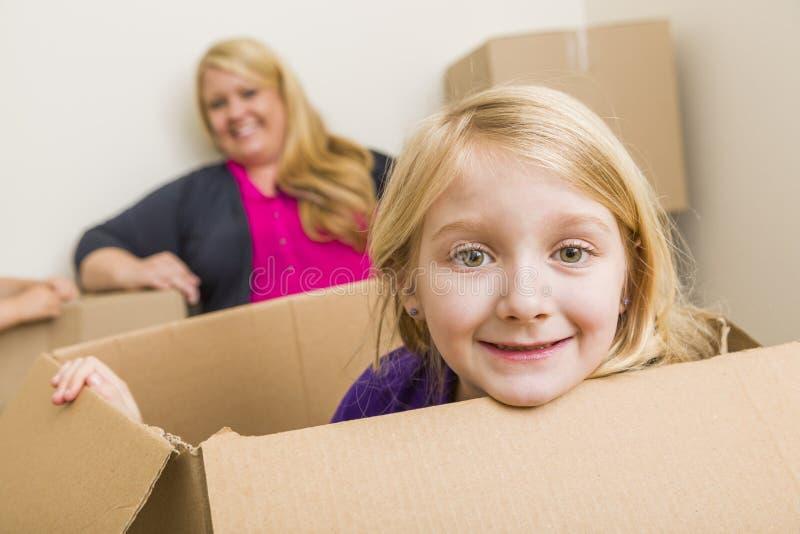Mãe nova e filha que têm o divertimento com caixas moventes imagens de stock royalty free
