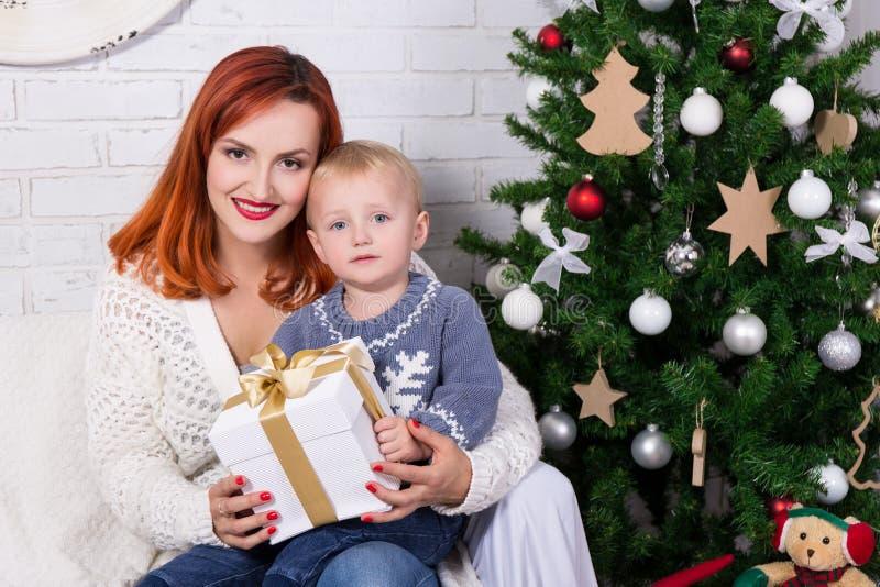 Mãe nova e filho pequeno na frente da árvore de Natal foto de stock