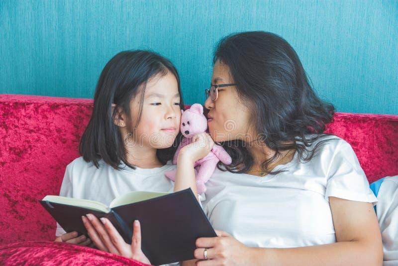Mãe nova e menina pequena da filha que leem um livro no sofá em foto de stock royalty free