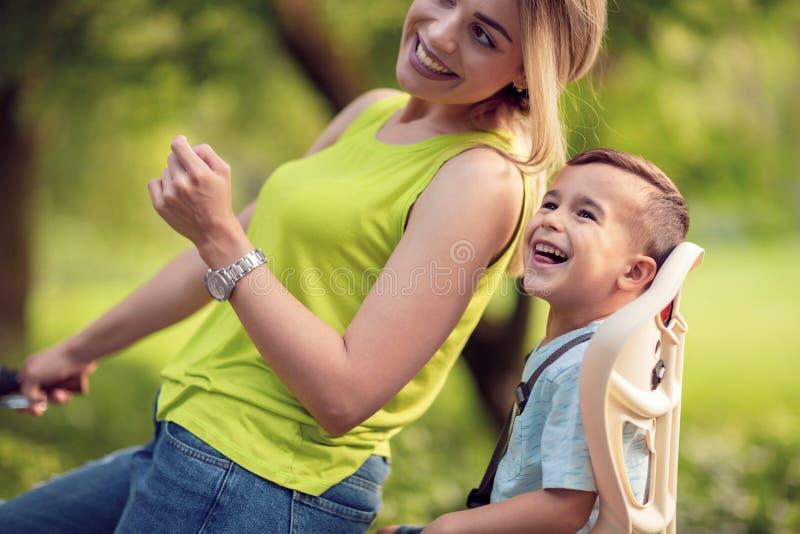 Mãe nova e menino que biking no dia morno do verão fotografia de stock