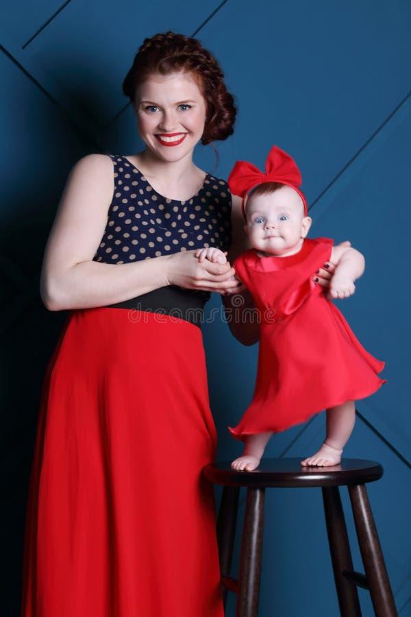 A mãe nova e o bebê bonito no tamborete levantam no estúdio azul imagem de stock