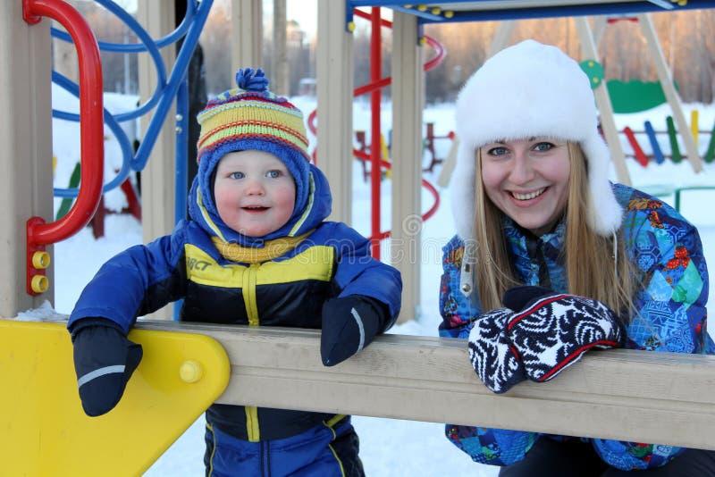 A mãe nova e o filho que andam no inverno estacionam fotos de stock royalty free
