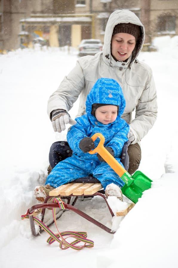 Mãe nova e rapaz pequeno que apreciam o passeio do trenó Sledding da criança Pequeno trenó da equitação da criança da criança Jog imagem de stock