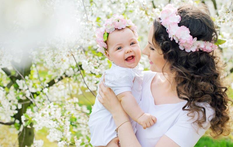 Mãe nova e seu bebê pequeno que relaxam em um pomar da mola fotos de stock royalty free