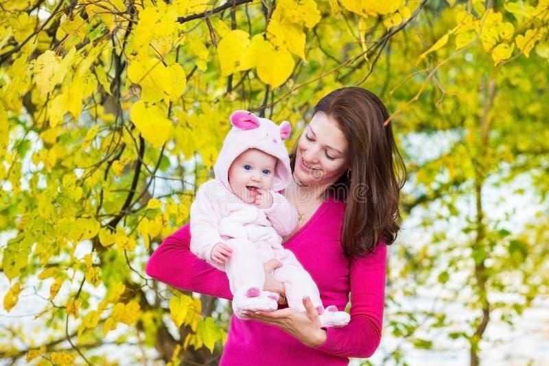A mãe nova e seu bebê que andam no atumn estacionam fotografia de stock royalty free