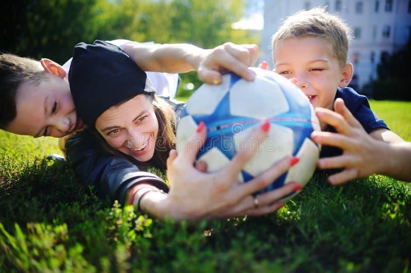 Mãe nova e seus rapazes pequenos que jogam um jogo de futebol no dia de verão ensolarado fotos de stock royalty free