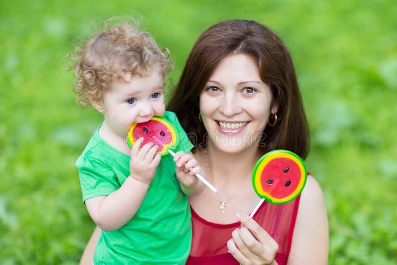 Mãe nova e sua filha do bebê que comem candys fotografia de stock