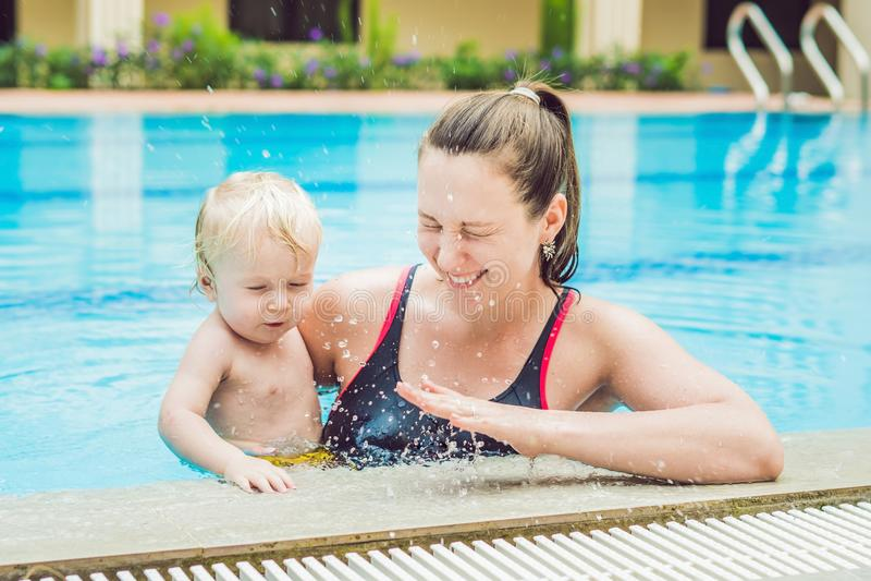 A mãe nova ensina seu filho pequeno, como nadar em uma piscina imagens de stock
